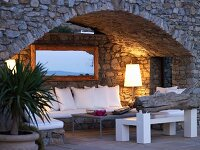 Cosy atmosphere in arched niche in stone house facade with sofa and modern coffee table next to standard lamp