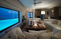 Spacious sofa combination and coffee table in front of panoramic window with view of illuminated pool
