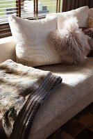 Light couch with cozy, fur look pillows and throw