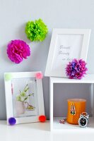 Pompoms decorating picture frames & wall
