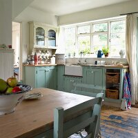 Old, pastel blue kitchen-dining room in English country-house style; bowl of apples on dining table in foreground
