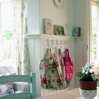 Floral fabric bags hanging from ornamental coat rack on wood-panelled wall in rustic kitchen-dining room