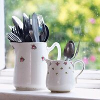 Large and small items of cutlery in two old china jugs with floral patterns in front of window