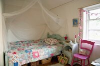 Romantic, country-house bed with patchwork quilt and draped mosquito net in child's bedroom