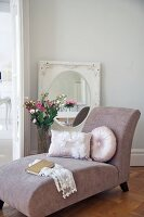 Cushions on dusky pink chaise longue, vase of flowers and oval mirror