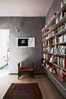 Antique stool and Oriental rug in front of grey marbled wall; letter ornaments on narrow, floating bookshelves to one side