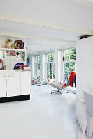 Open-plan, white interior with various colourful accessories