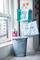 Zinc bin with lid and printed shopping bags in kitchen next to sash window