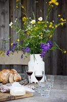Cheese, bread, two glasses of red wine and a milk churn of wild flowers on a rustic wooden table