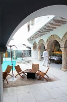 View of pool and outdoor furniture in Oriental hotel courtyard through rounded arch