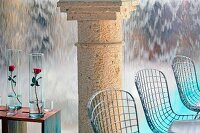 Wire chairs, roses in glass vases on side tables and stone columns in front of wall with waterfall effect