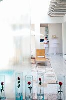 Red roses in glass vases on floor of courtyard and member of staff in entrance to spa