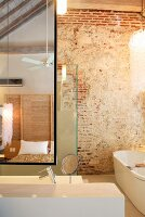 Designer bathroom furnishings, rustic brick wall and view of bed reflected in mirror