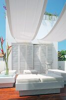 Elegant outdoor furniture with white leather upholstery under white awnings on roof terrace
