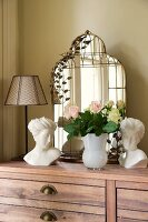Bouquet of roses, busts and mirror on chest of drawers