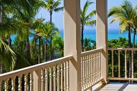 Veranda with white, carved wooden balustrade and sea view through palm trees