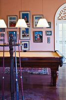 Billiard room with framed pictures on apricot walls