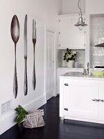 White-painted fitted kitchen with industrial-style pendant lamp and photo-realistic cutlery mural on wall