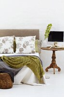 Blankets and scatter cushions on modern double bed with headboard next to rustic wooden side table with turned leg