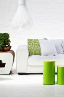 Green-varnished, cylindrical side tables in front of white sofa and designer pendant lamp with white slatted lampshade