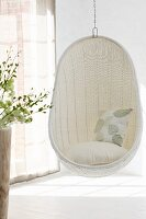 Comfortable, white wicker hanging chair in corner of room next to window with closed, translucent curtains and pattern of light and shadow on floor