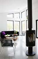 Free-standing log burner next to modern Spaghetti chair in open-plan interior with lounge area in eclectic mix of styles