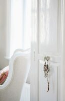 Open, white-painted interior door with costume jewellery hanging from doorknob and view of traditional armchair beyond