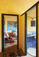 Corner of hallway with yellow walls, rug and view through open door into child's bedroom and bathroom