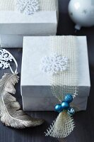Christmas present in gift box with stylised snowflake and miniature turquoise baubles on net ribbon