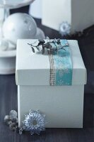Festive gift box with pastel snowflake-patterned ribbon and silver, glittery leaves