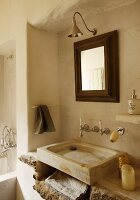 Simple, stone, counter-top wash basin with vintage, wall-mounted tap fittings and framed mirror in rustic bathroom
