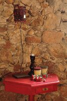 Retro table lamp on side table painted deep pink against old stone wall