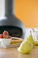 Fresh fruit on a table with a pot-bellied stove in the background