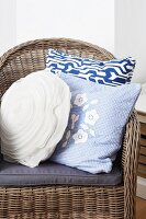 Wicker chair with blue and white scatter cushions