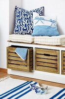 White seat cushions and blue and white scatter cushions on storage bench