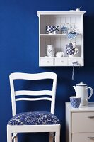 Crockery on Dutch-style kitchen shelving, coffee set on small cabinet and kitchen chair