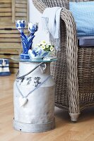 Dutch-style ornaments on milk churn converted into side table and wicker chair with scatter cushions