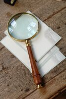 Magnifying glass and postcards with old-fashioned motif of couple on old table top