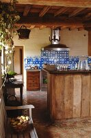 Rustic kitchen with antique blue wall tiles and simple wooden fronts combined with vintage-effect terracotta tiles
