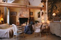 Rococo-style armchair and sofa around table draped with table cloth in rustic living room with exposed wooden beams