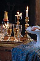 Full champagne glasses on tray in front of lit candles in brass candlesticks and china dish of confectionery on tablecloth