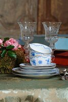 Stack of blue and white painted teacups and saucers in front of etched crystal glasses