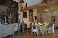 Rococo romantic atmosphere within old walls - long candlelit table festively set and surrounded by antique flea-market finds