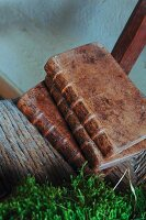 Worn antiquarian books with leather covers on woven seat of old chair