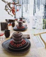 A table laid for dessert - Baumkuchen (German layer cakes) with trusses of redcurrants on a set of dark brown ceramic dishes