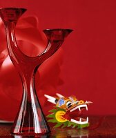 Two-armed, red glass candlestick and plastic toy against red background