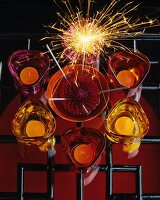 Top view of still-life with glass tealight holders in various shades of red and sparkler on black metal lattice