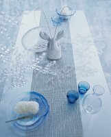 Glasses and glass dishes, some blue, on table runner