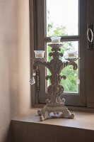 Vintage candlestick on sill of lattice window