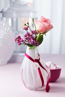 Rose & waxflowers in glass vase decorated with satin ribbon & button